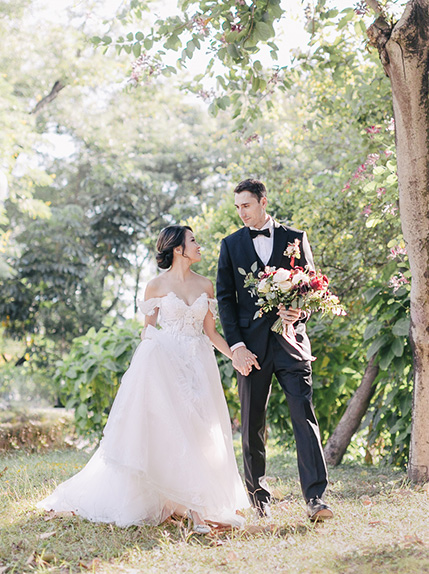 couple walk holding hands in wedding attire