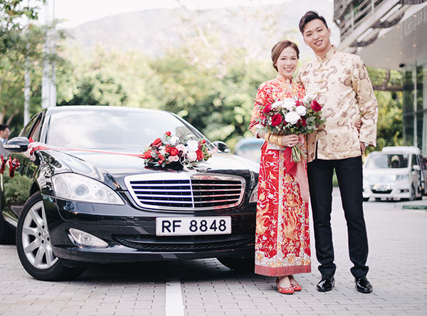 bride and groom posing in front of wedding car