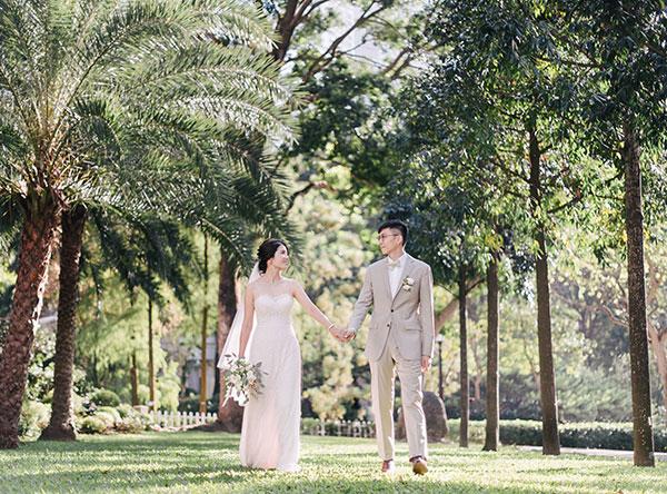bride and groom walking through wedding venue gard
