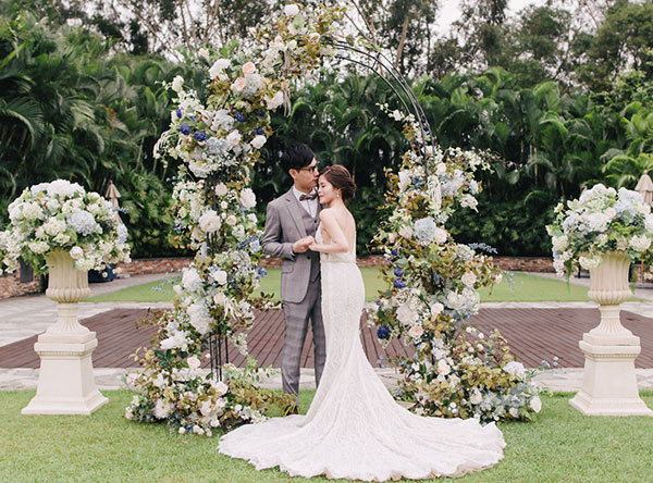 couple embrace in front of wedding arch