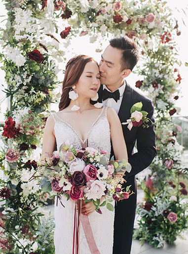 couple pose in front of floral wedding arch