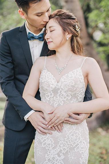 groom hugs his bride from behind
