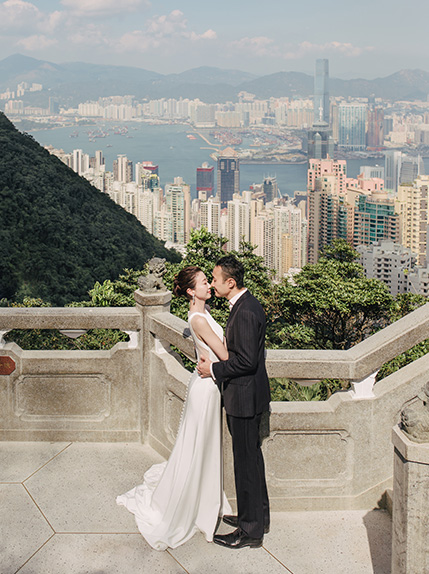 couple embrace with hong kong in the background