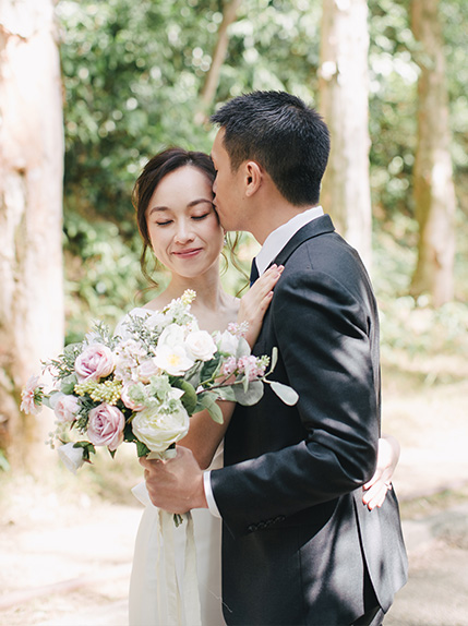 groom kisses bride holding floral bouquet