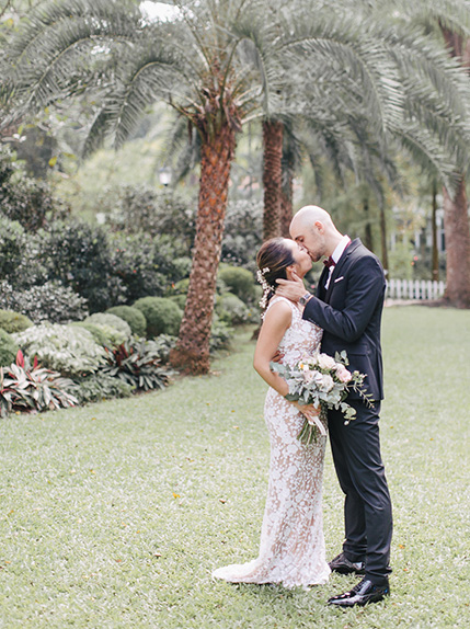 couple kissing in front of palm trees