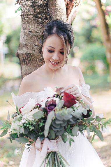 bride looking at wedding bouquet