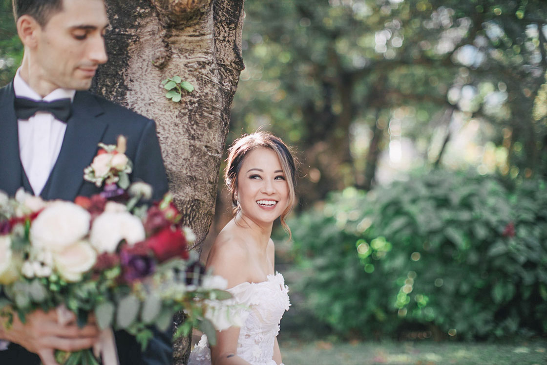 bride and groom posing next to a tree during wedding day
