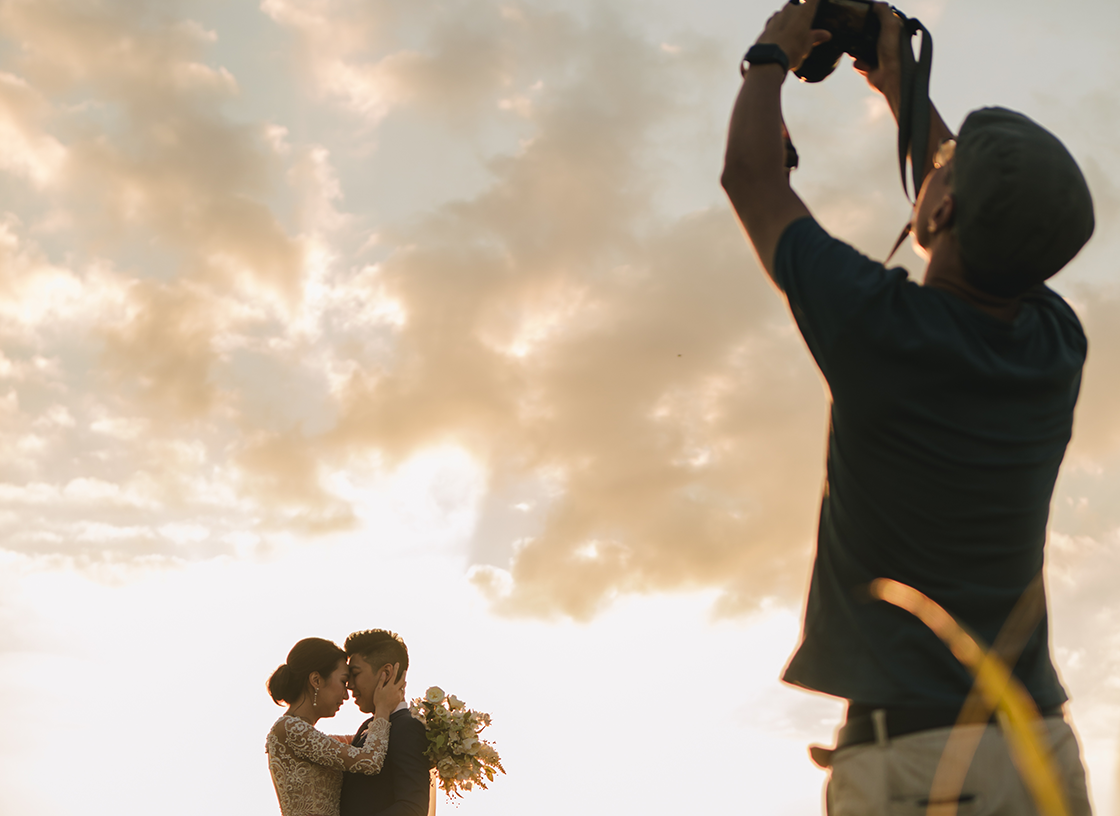 photographer taking photo of married couple